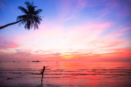 Silhouette young woman in a jump on the sea beach at sunset (concept of long-awaited vacation) photo