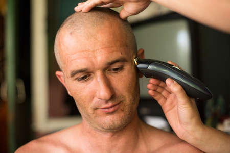 bald man: Hairdresser shaving man with hair trimmer.
