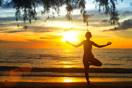 Young woman practicing yoga at sunset on the coast of Thailand photo