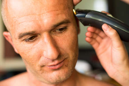 Close-up: Hairdresser makes hairstyle bald man.