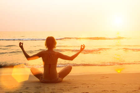 Young girl practicing yoga on the beach. photo