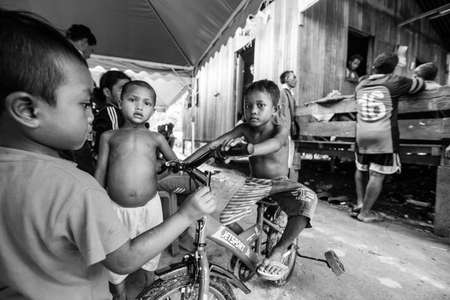 jah: BERDUT, MALAYSIA - APR 8: Unidentified children Orang Asli in his village (bw photo) on Apr 8, 2013 in Berdut, Malaysia. More than 76% of all Orang Asli live below the poverty line, life expectancy - 53 years old.