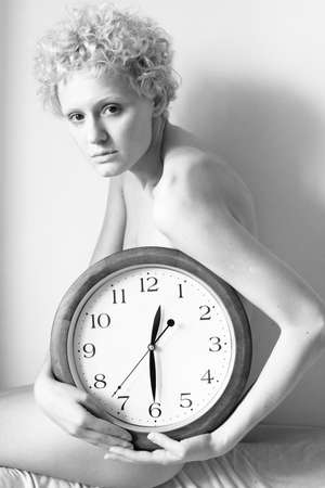 scrawny: Young scrawny woman with big clock in hands (bw photo)
