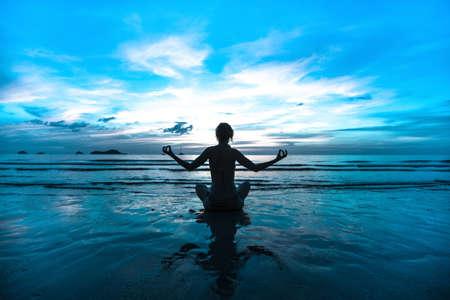 Sunset yoga woman on sea coast (in cold colors) photo