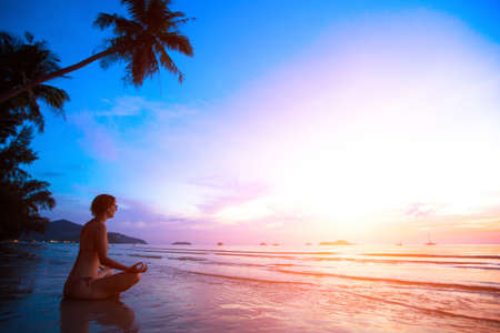 Young woman practicing yoga on the beach at sunset photo