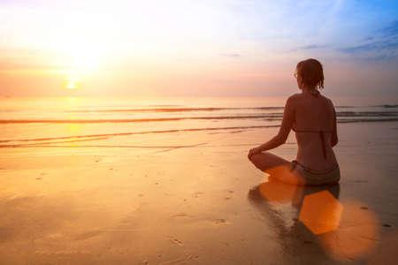 sunrise beach: Silhouette of a woman yoga on sea sunset Stock Photo