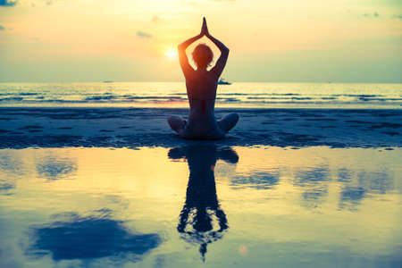 yoga silhouette: Yoga woman sitting in lotus pose on the beach during sunset, with reflection in water (cross-process style) Stock Photo