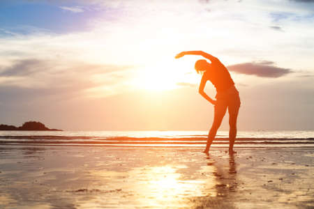 Silhouette young woman, exercise on the beach at sunset photo