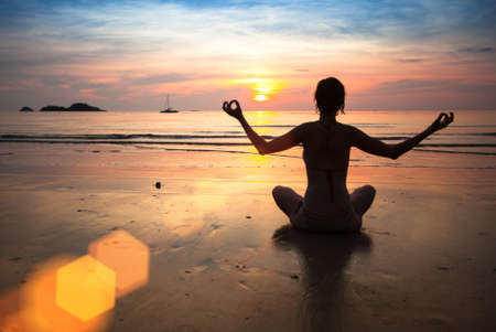Silhouette young woman practicing yoga, on the beach at sunset photo