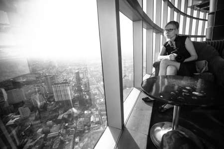 A young woman sitting by the window at skyscraper, black and white photo. photo