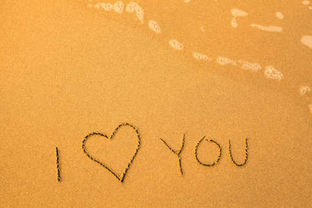 I Love You - text written by hand in sand on a beach, with a soft wave. photo