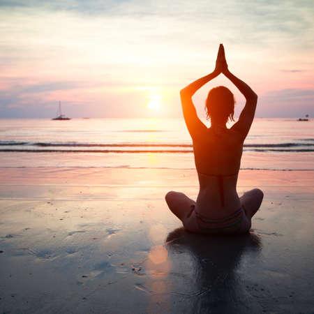 gesundheit: Silhouette einer Frau Yoga am Meer Sonnenuntergang.