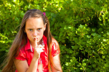hushing: Shh. secret! Beautiful young girl with her finger over her mouth, hushing.