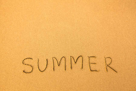 Summer, text written by hand in sand on a beach. photo