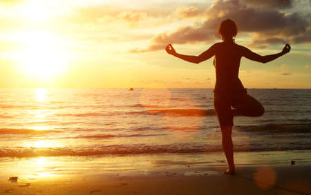 Yoga woman on the beach during sunset. photo