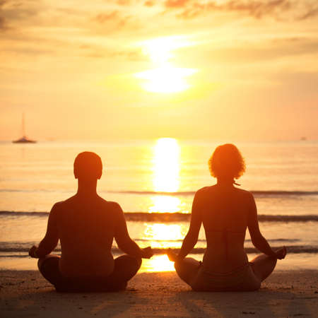 Yoga practice: a young couple sitting on the beach of the sea in the lotus position at sunset. photo