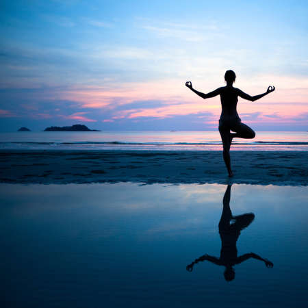 Woman practicing yoga on the beach after sunset. photo