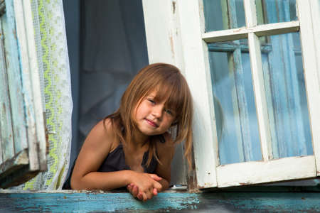 Little girl looks out the window rural house  photo