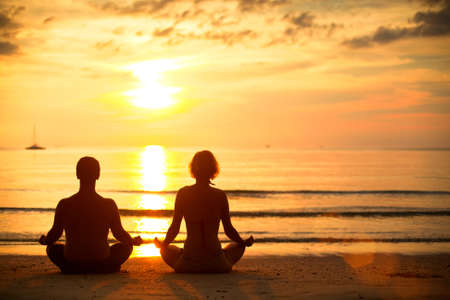 Young couple practicing yoga on the beach at sunset. Stock Photo