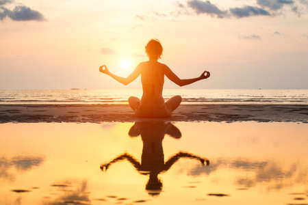 Yoga woman sitting in lotus pose on the beach during sunset, with reflection in water. Stock Photo - 22220353