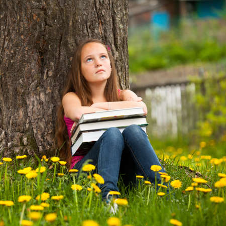 Tired teen girl with books in the village photo