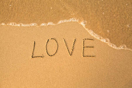 Love - text written by hand in sand on a beach, with a blue wave photo