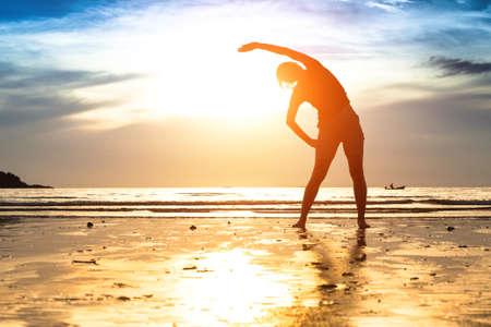lifestyle: Silueta de mujer joven, hacer ejercicio en la playa al atardecer