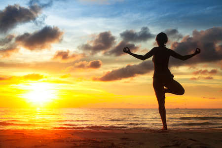 thai yoga: Woman practicing yoga on the beach during the sunset.