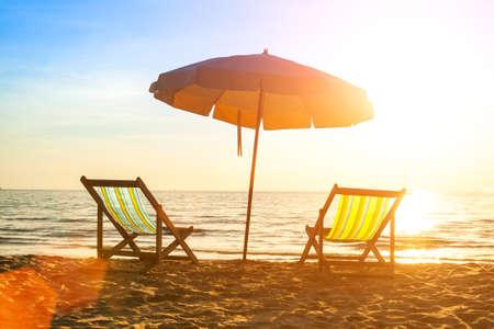 Beach loungers on deserted coast sea at sunrise. Stock Photo