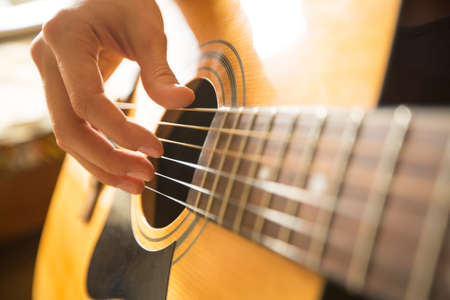 western background: Female hand playing on acoustic guitar. Close-up.
