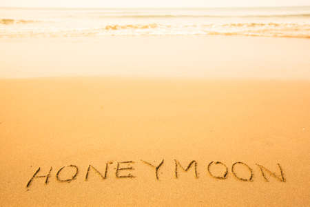 Honeymoon - text written by hand in sand on a beach, with a soft wave. photo