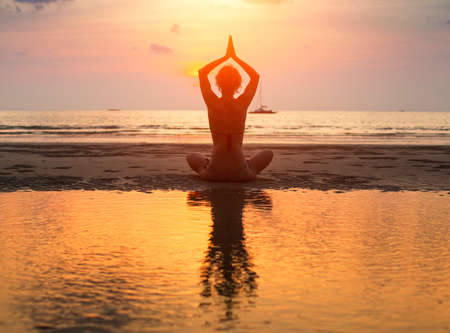 Yoga woman sitting in lotus pose on the beach during sunset with reflection in water. Stock Photo - 23077968