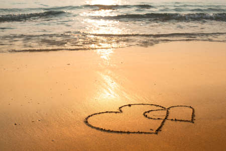 evoking: Hearts drawn on the sand of the sea beach. Stock Photo
