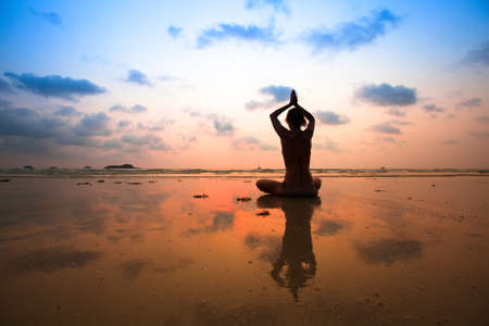Yoga woman sitting in lotus pose on the beach during sunset, with reflection in water. Stock Photo - 23077979
