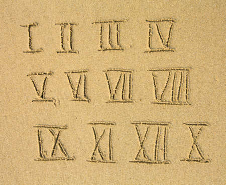 Roman numerals written on a sandy beach. (from 1 to 12) photo