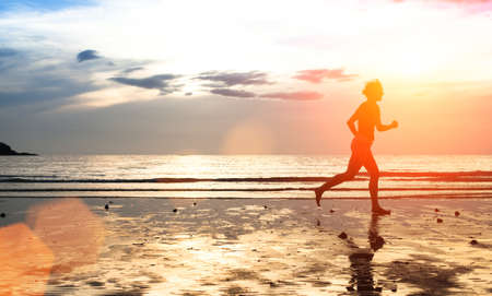 Silhouette of a young woman jogger at sunset on the seashore (with space for text)