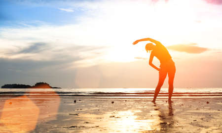 Silhouette young woman, exercise on the beach at sunset (with space for text) photo