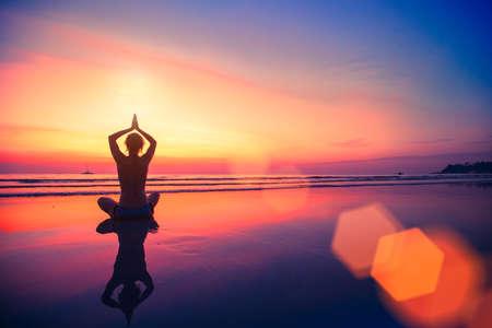 yoga beach: Silhouette yoga woman sitting on sea coast at beautiful sunset.