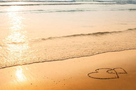 evoking: Hearts drawn on the sand of a beach, soft wave of the sea Stock Photo