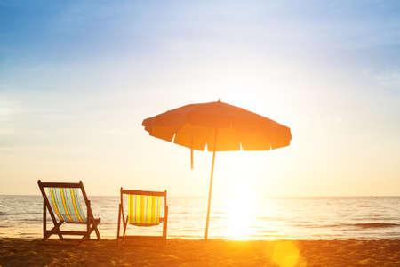 beach chair: Pair of beach loungers on the deserted coast sea at sunrise. Stock Photo