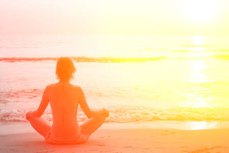 Yoga woman sitting in lotus pose on the beach during sunset, in bright colors. photo