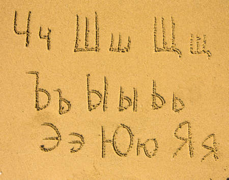 ch: Russian alphabet (from Ch to Ja) written on a sand beach. Stock Photo