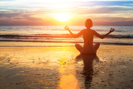 Silhouette of woman practicing yoga on the beach during sunset. photo