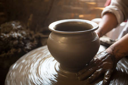 Close-up of hands working clay on potters wheel.    photo