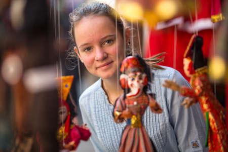singing bowls: Teen-girl in a Indian souvenir shop.