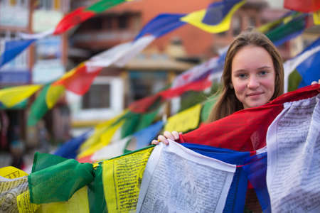 Teen-girl in Buddhist monastery, with Buddhist prayer flags flying.  photo