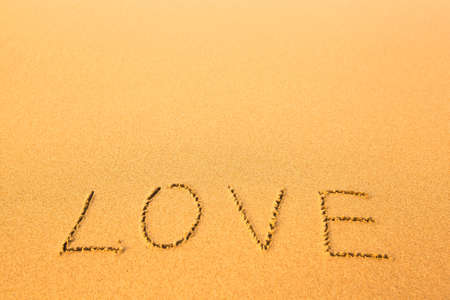 Love - text written by hand in sand on a beach. photo