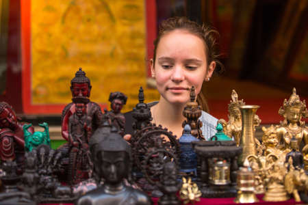singing bowls: Teen-girl in a Asian souvenir shop.