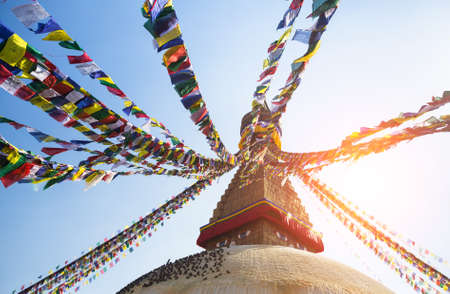 Prayer flags flying against the sun from the Boudhanath Stupa - symbol Kathmandu, Nepal. photo