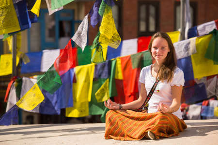Young girl sitting in the Lotus position on Buddhist stupa, prayer flags flying in the background. photo